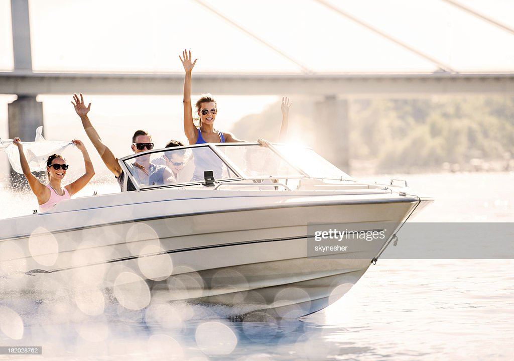 Cheerful young people riding in a speedboat.
