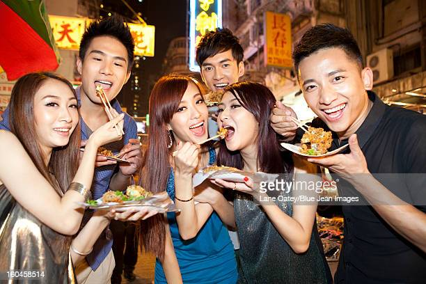 Cheerful young people trying some local snacks on Temple Street of Hong Kong, night view