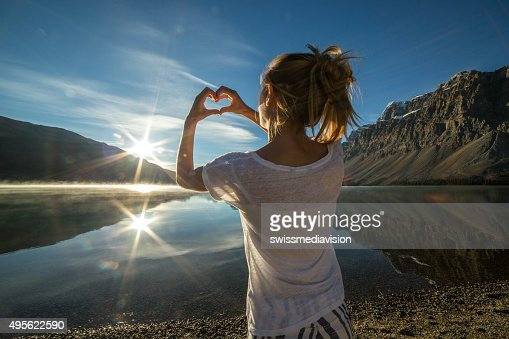 Cheerful young woman by the lake loving nature stock photo for Cheerful nature