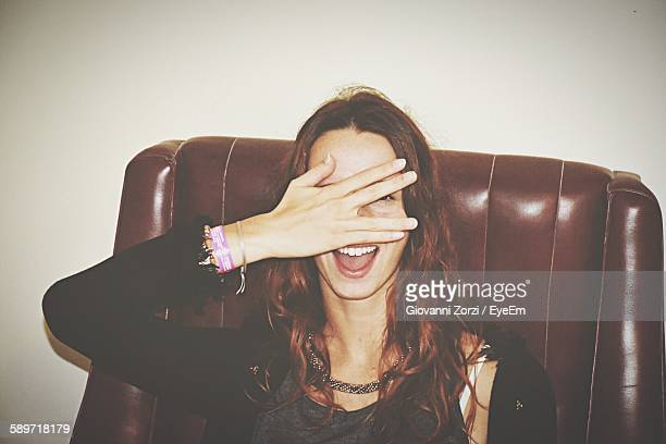 Cheerful Young Woman Covering Face Sitting On Chair At Home