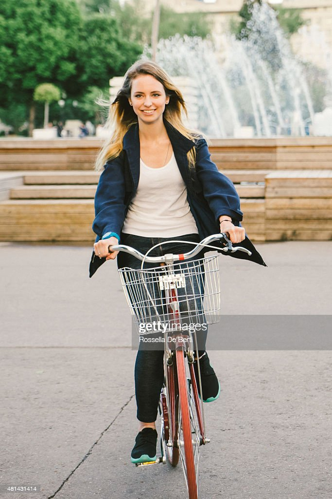 Cheerful Young Woman Cycling In The Park