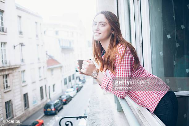 Cheerful young woman drinking coffee