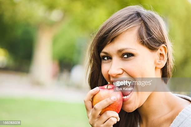 Alegre joven mujer comiendo una manzana