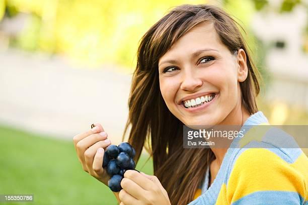 Gaie jeune femme manger le raisin