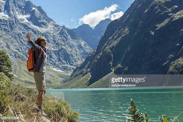 Cheerful young woman hiking reaches the lake Marian, arms outstretched
