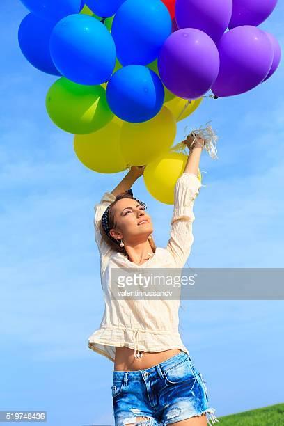 Fröhliche junge Frau halten Haufen bunte Ballons