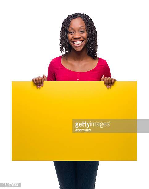 Cheerful young woman holding a yellow sign