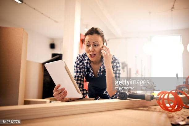 Cheerful young woman in carpenter workshop using phone