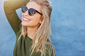 Cheerful young woman in sunglasses against blue background. Beautiful female model with long hair.
