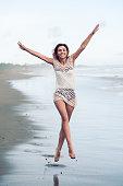 cheerful young woman jumping at beach