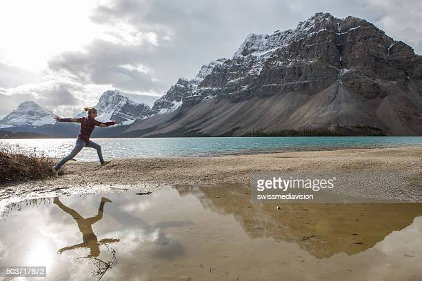 Cheerful young woman leaping mid-air by the lake