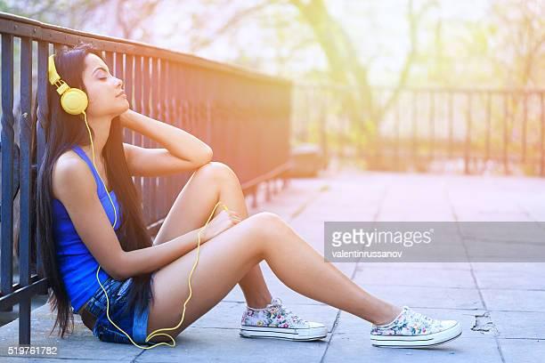 Gaie jeune femme écoutant de la musique en plein air