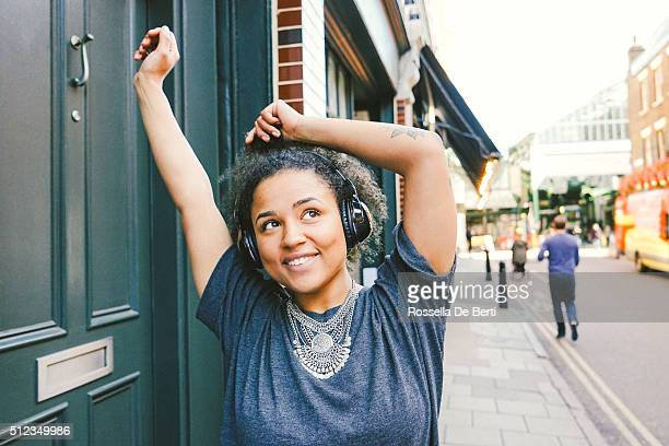 Fröhliche junge Frau, hören Musik, urbane Landschaft im Hintergrund
