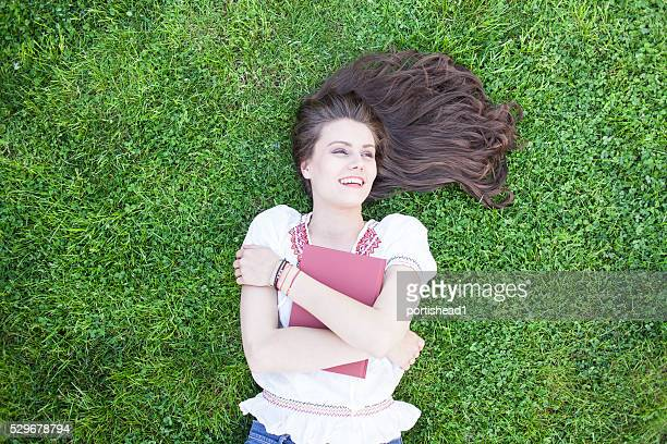 Cheerful young woman lying on grass and embracing a book