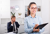 cheerful young woman manager holding cardboard and smiling in office