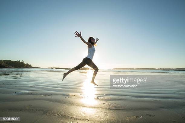 Cheerful young woman on beach jumping for joy and freedom