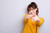 Portrait of cheerful young woman pointing finger at you