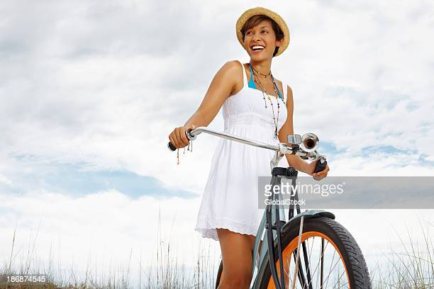 Cheerful, young woman riding bicycle on the beach against sky
