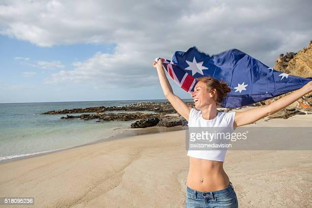 Cheerful young woman runs on beach holding Australian's flag