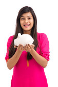 Cheerful young Woman Saves Money in Piggy bank on white background.