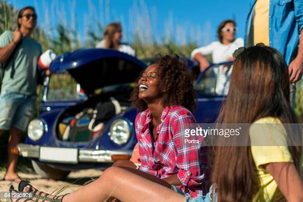 Cheerful young woman sitting by friend on field