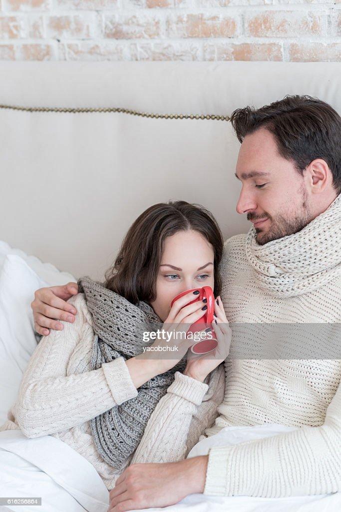 Cheerful young woman sitting near her boyfriend : Stock Photo