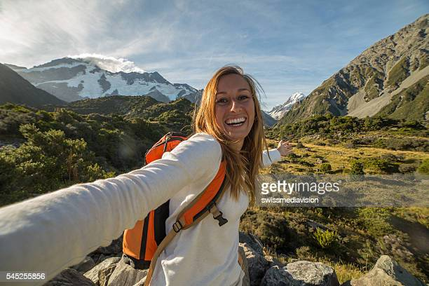 Cheerful young woman takes a self portrait on a mountain