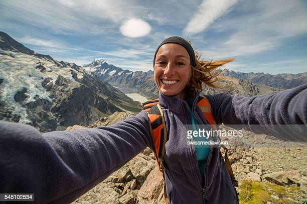 Cheerful young woman takes self portrait on mountain top