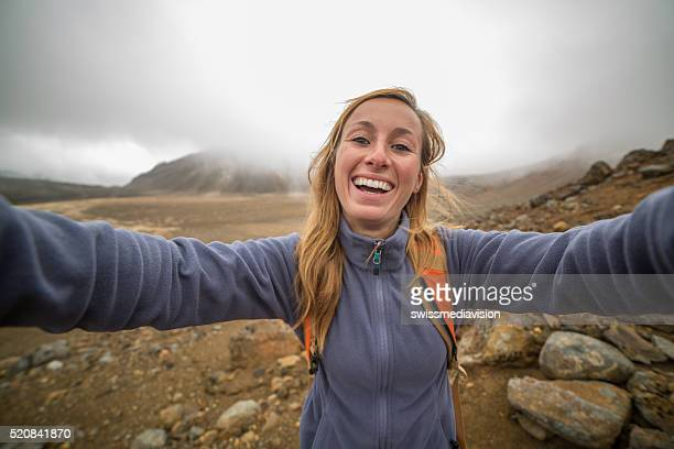 Cheerful young woman takes selfie portrait on Tongariro Alpine Crossing