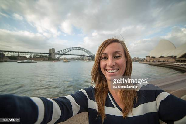 Cheerful young woman takes selfie portrait with Sydney harbor