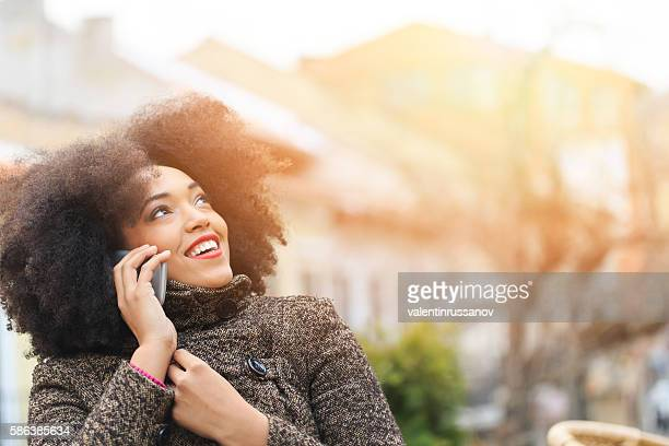 Cheerful young woman talking on the phone at street