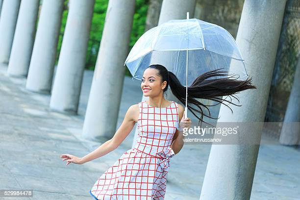 Cheerful young woman walking under the rain