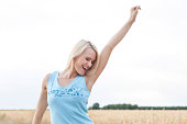 Cheerful young woman with arm raised standing against clear sky