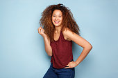Portrait of cheerful young woman with curly hair smiling against blue background