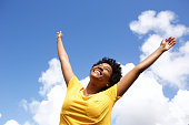 Portrait of cheerful young woman standing outside with her hands raised towards sky
