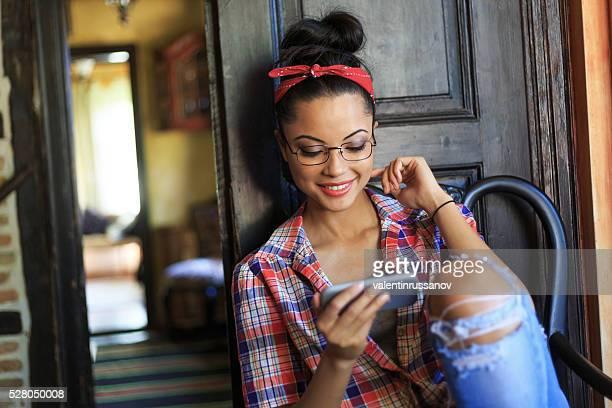Fröhliche Junge Frau mit Stirnband mit Telefon