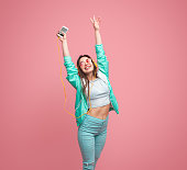 Stylish smiling female in casual outfit holding modern smartphone while standing with hands up and listening music through big yellow earphones on pink background