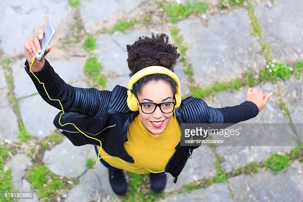 Joyeuse jeune femme avec un casque écouter de la musique avec jaune