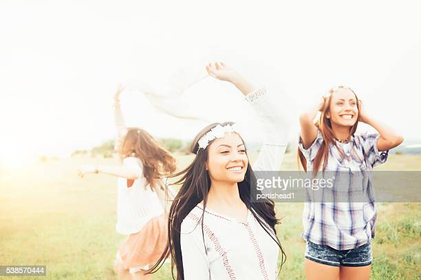 Cheerful young women dancing in the grassland