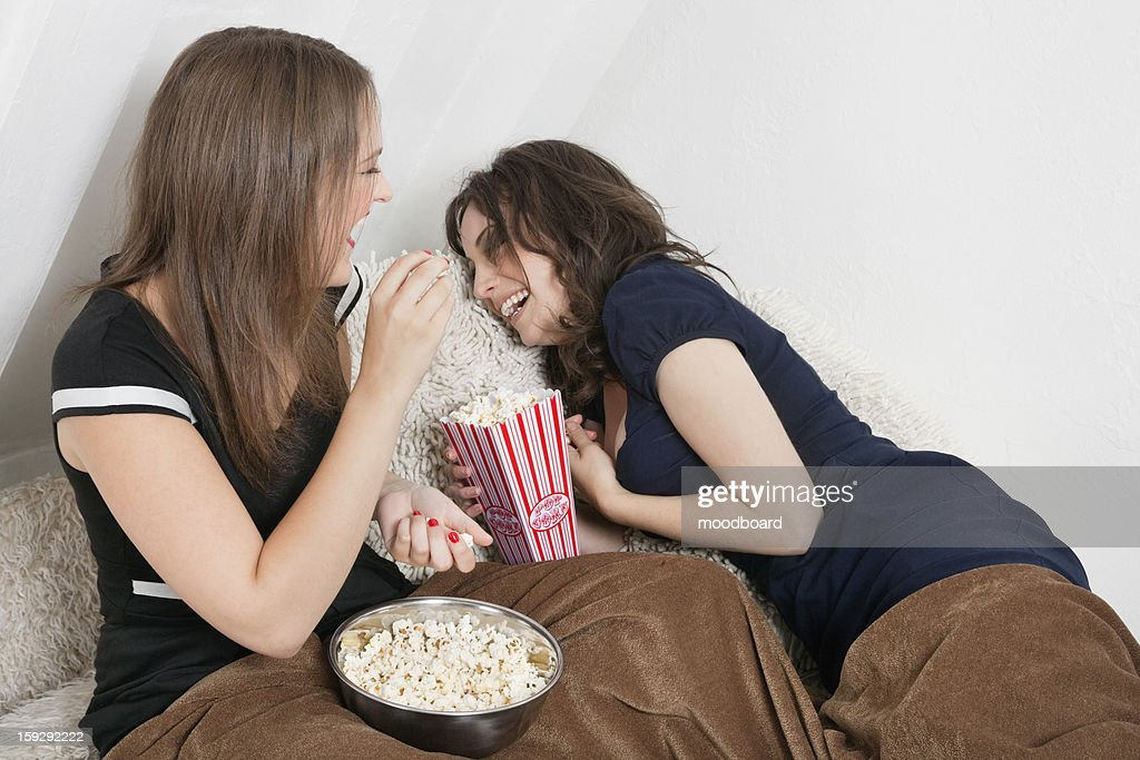 Cheerful young women eating popcorn in bed : Stock Photo