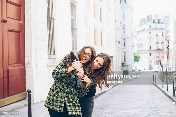 Cheerful young women having fun and embracing on street
