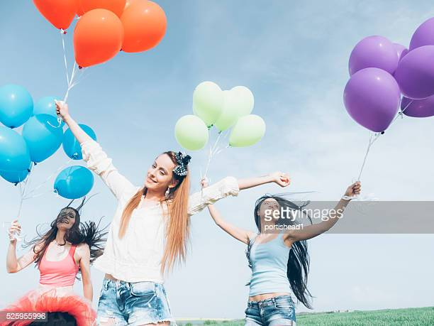 Cheerful young women holding a bunch of balloons