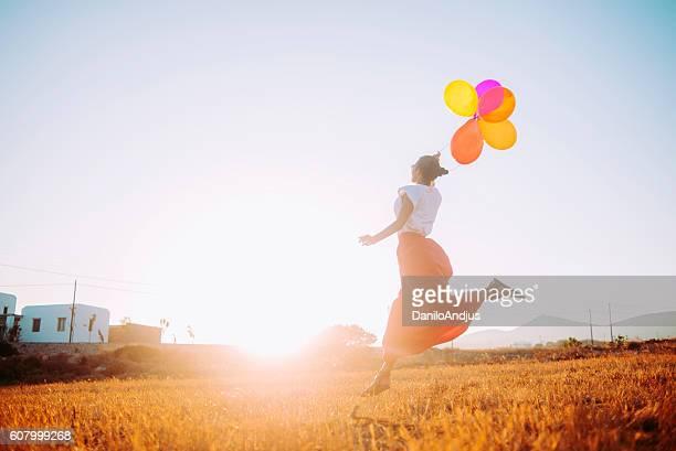 cheerfull woman running threw the field holding balloons