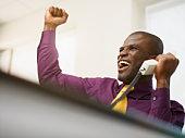 Cheering Black businessman holding telephone
