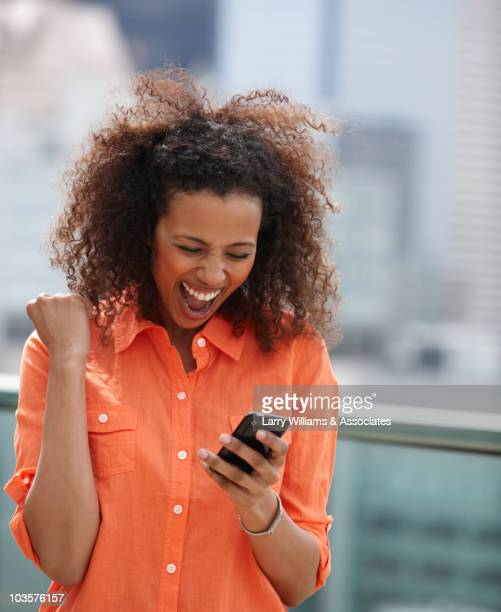 Cheering Black woman text messaging on cell phone