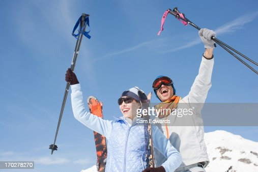 Cheering couple holding skis and poles : Stock Photo