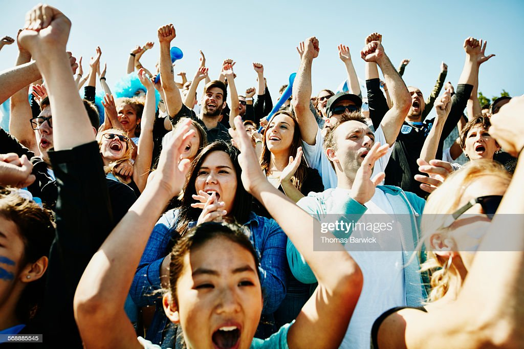 cheering crowd of soccer fans in stadium stock photo