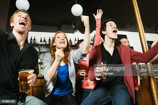 cheering fans watch football on television in bar