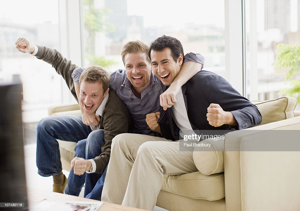 Cheering friends watching television : Stock Photo