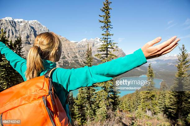 Cheering hiker at mountain top, arms outstretched